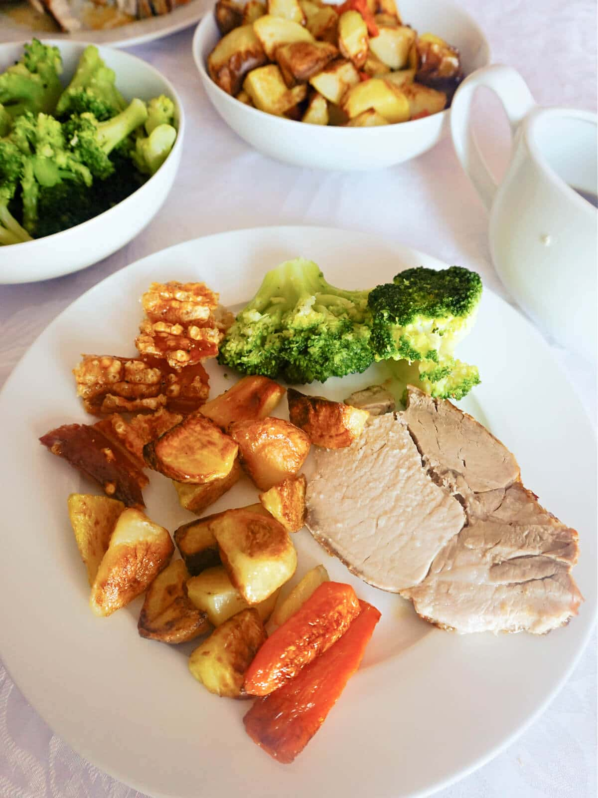 A white plate with a slice of roast pork, roasted vegetables and broccoli