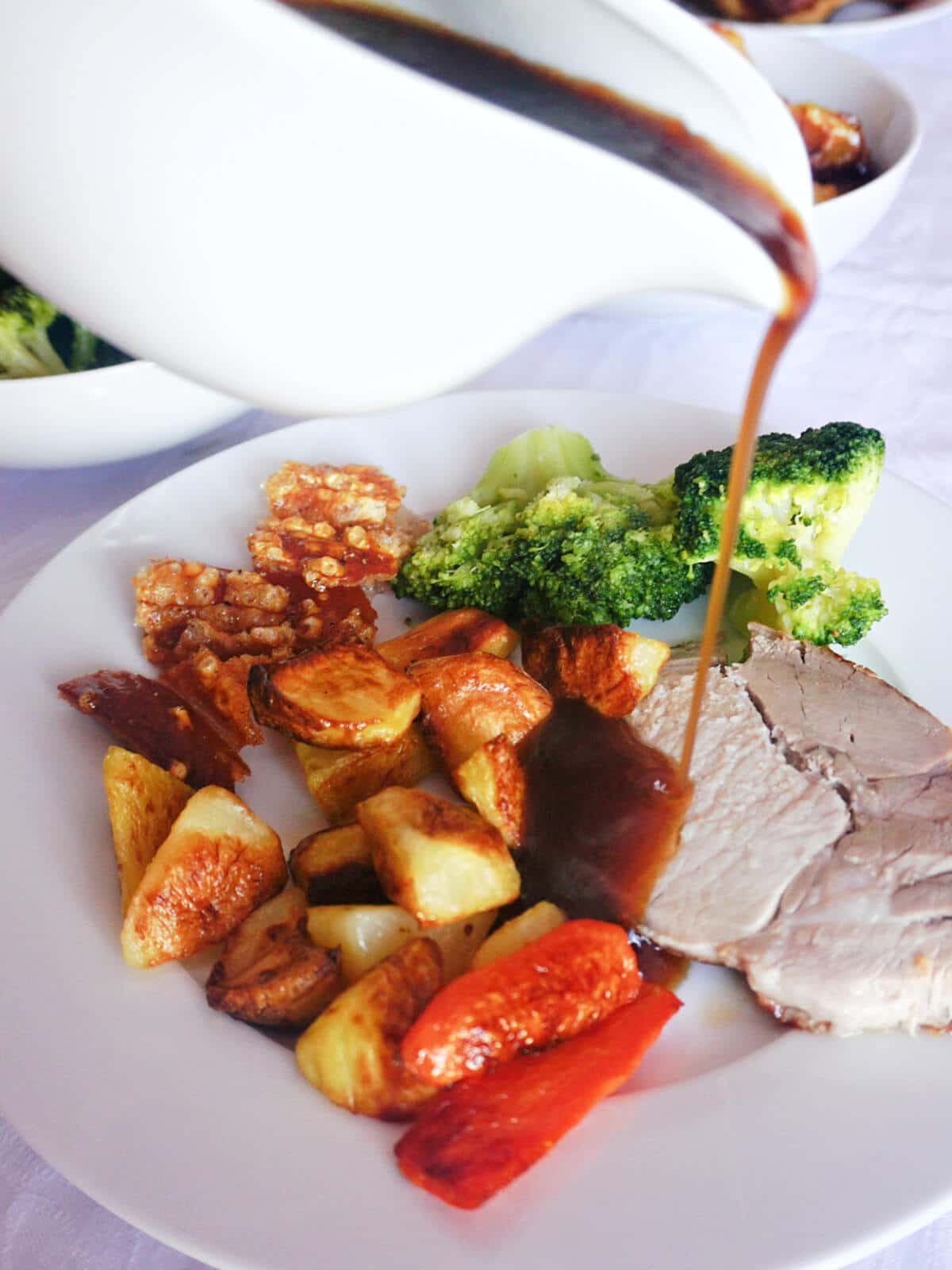 Gravy being poured over a slice of roast pork with vegetables on a white plate