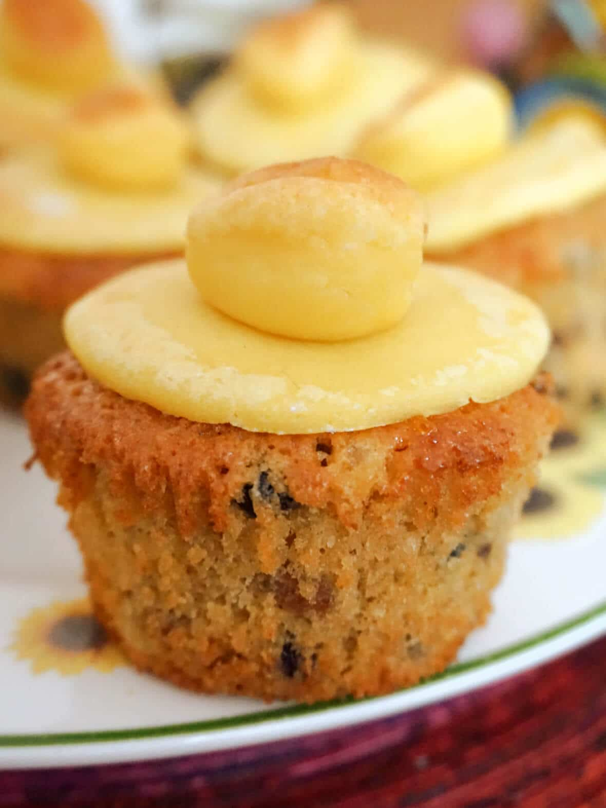 A simnel cupcake on a white plate with more cupcakes in the background