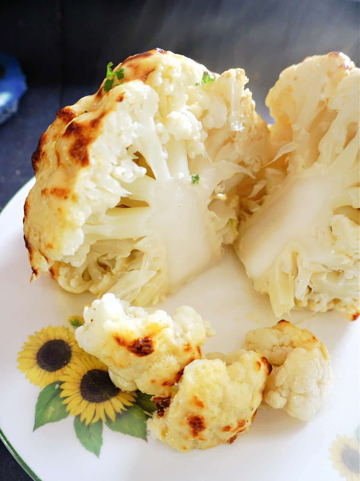 A whole roasted cauliflower cut into 2 halves and 2 florets on a white plate