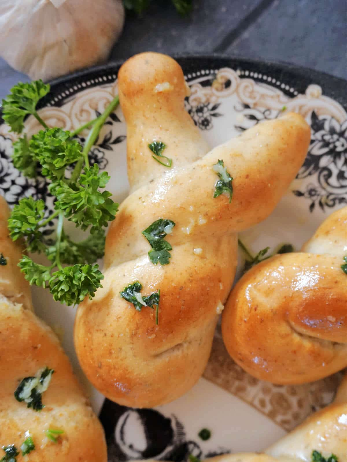 Overhead shot of a bunny-shaped garlic knot on a plate with fresh parsley