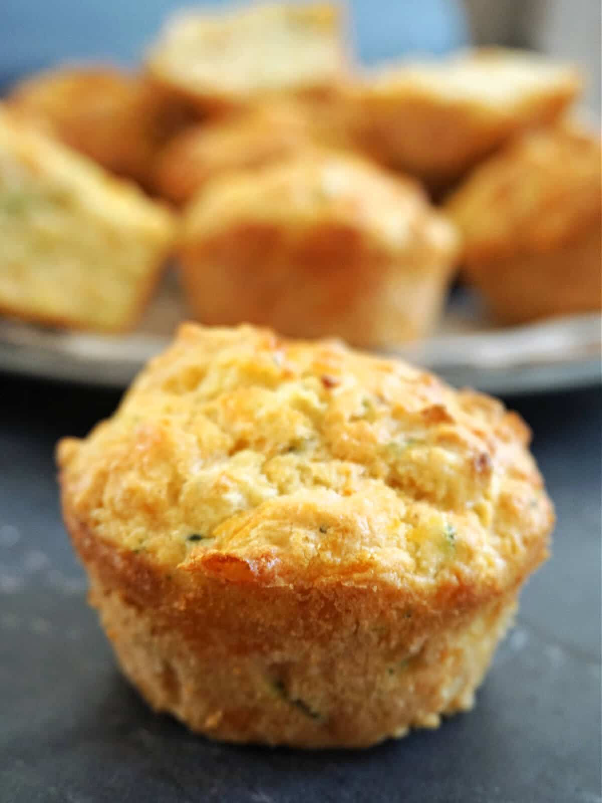 Close-up shot of a carrot and courgette muffins with more muffins in the background