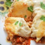 Close-up shot of enchiladas on a white flowery plate
