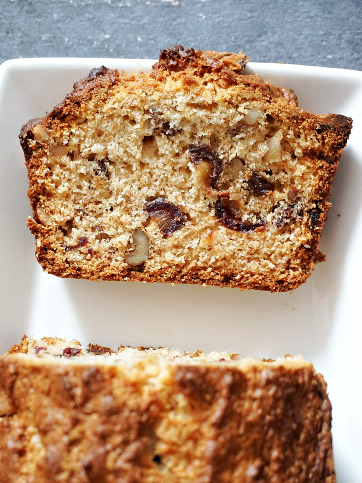 A slice of walnut and date cake on a white plate