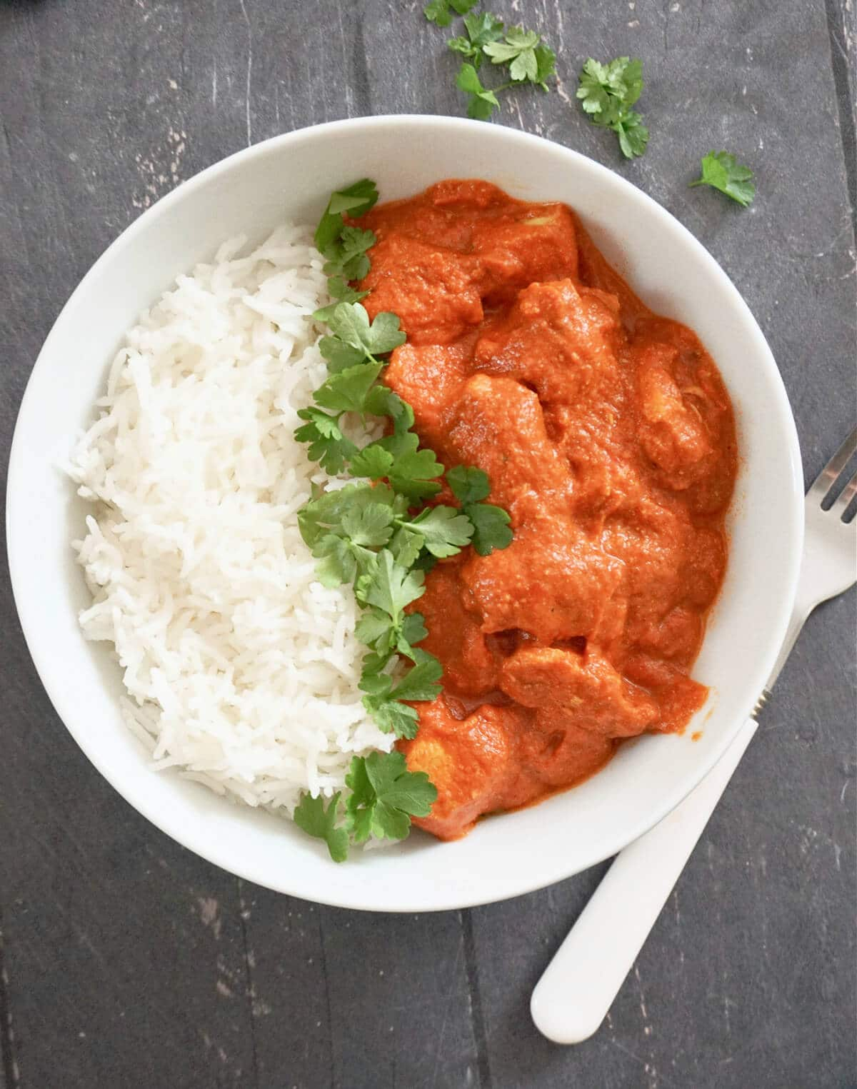 Overhead shot of a white bowl with butter chicken, basmati rice and fresh parsley leaves