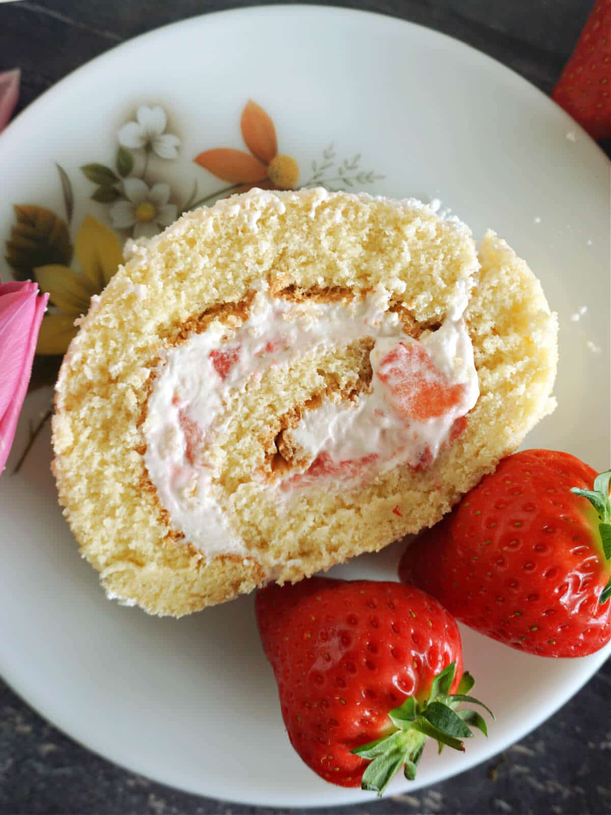 Overhead shot of a slice of strawberry cake roll on a white plate