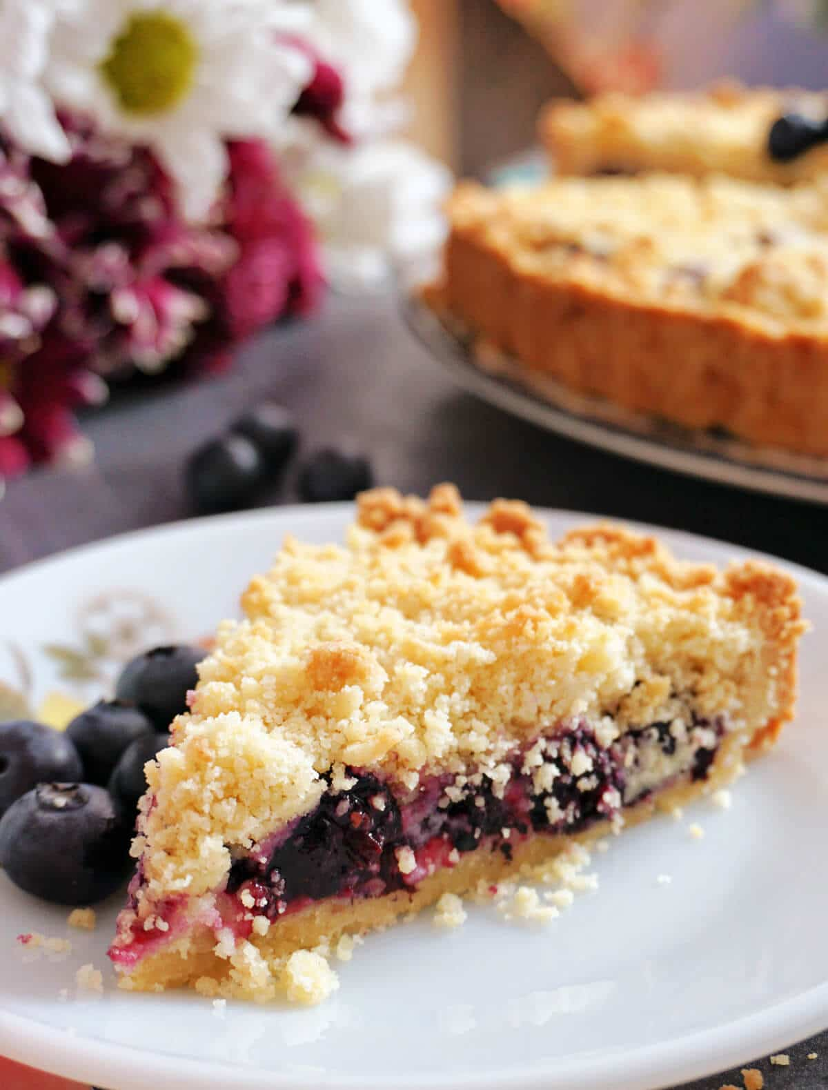 A slice of blueberry pie on a white plate with blueberries around