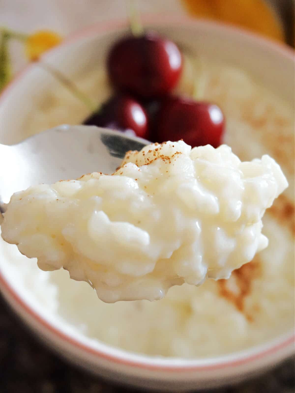 A spoonful of rice pudding over a bowl with more pudding and 3 cherries