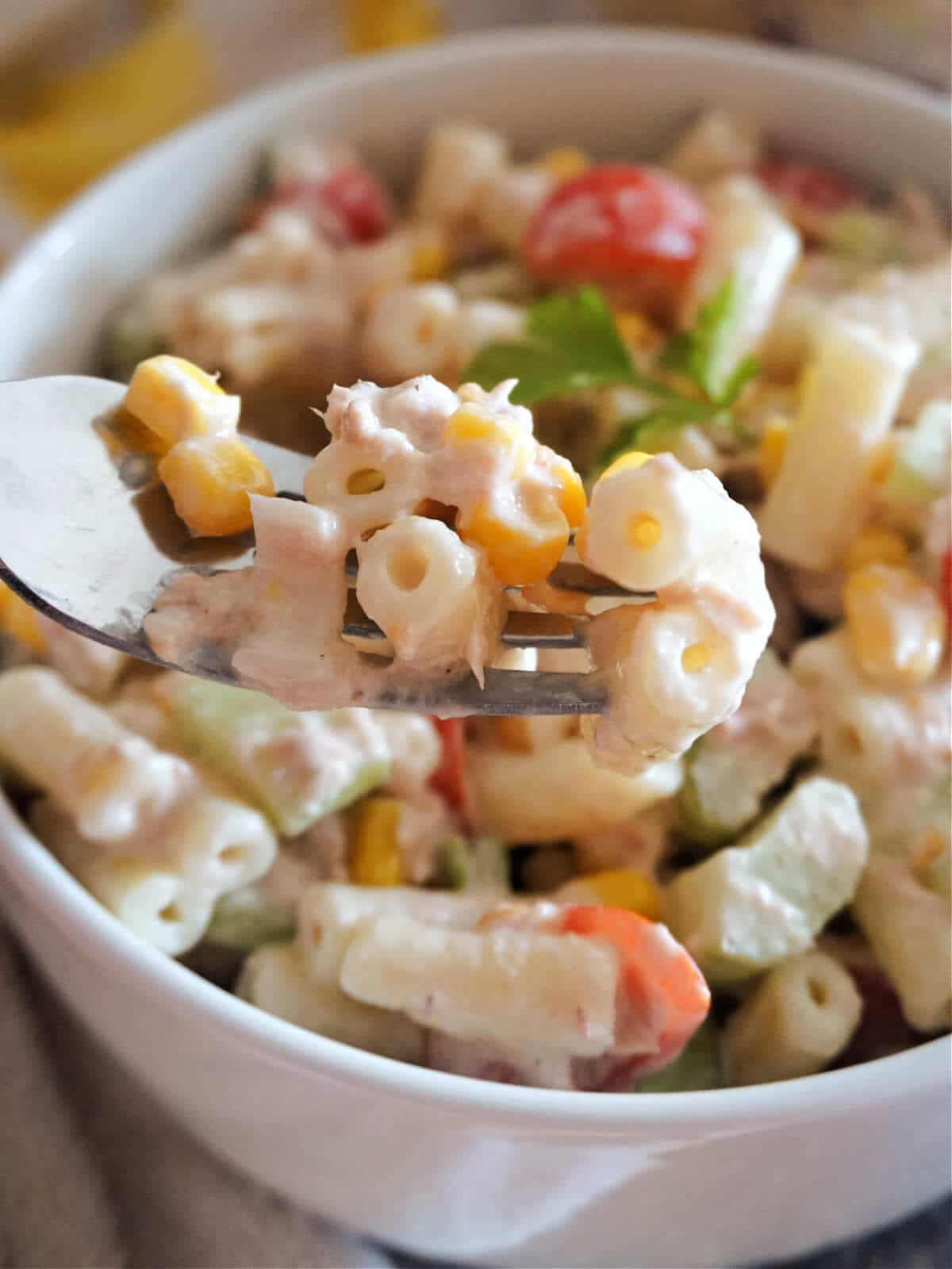 Close-up shot of a white bowl with tuna pasta salad and a fork in it