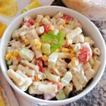 A white bowl with pasta salad with tuna and veggies
