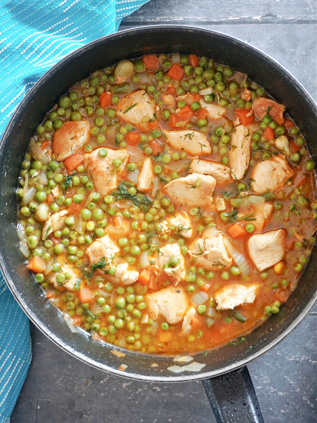 Overhead shot of a pan with chicken pieces and pea stew