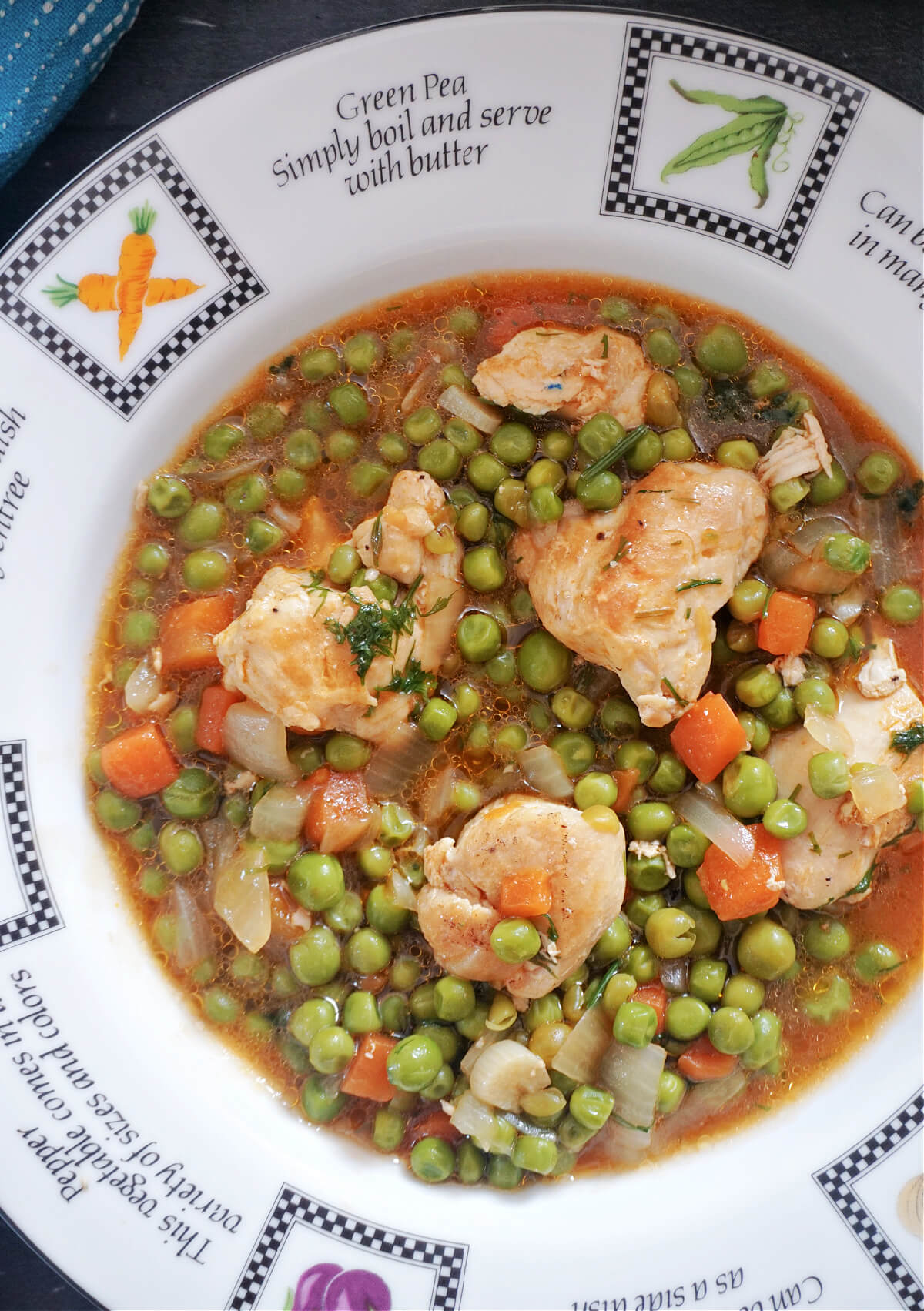 Close-up shot of a white plate with chicken and pea stew