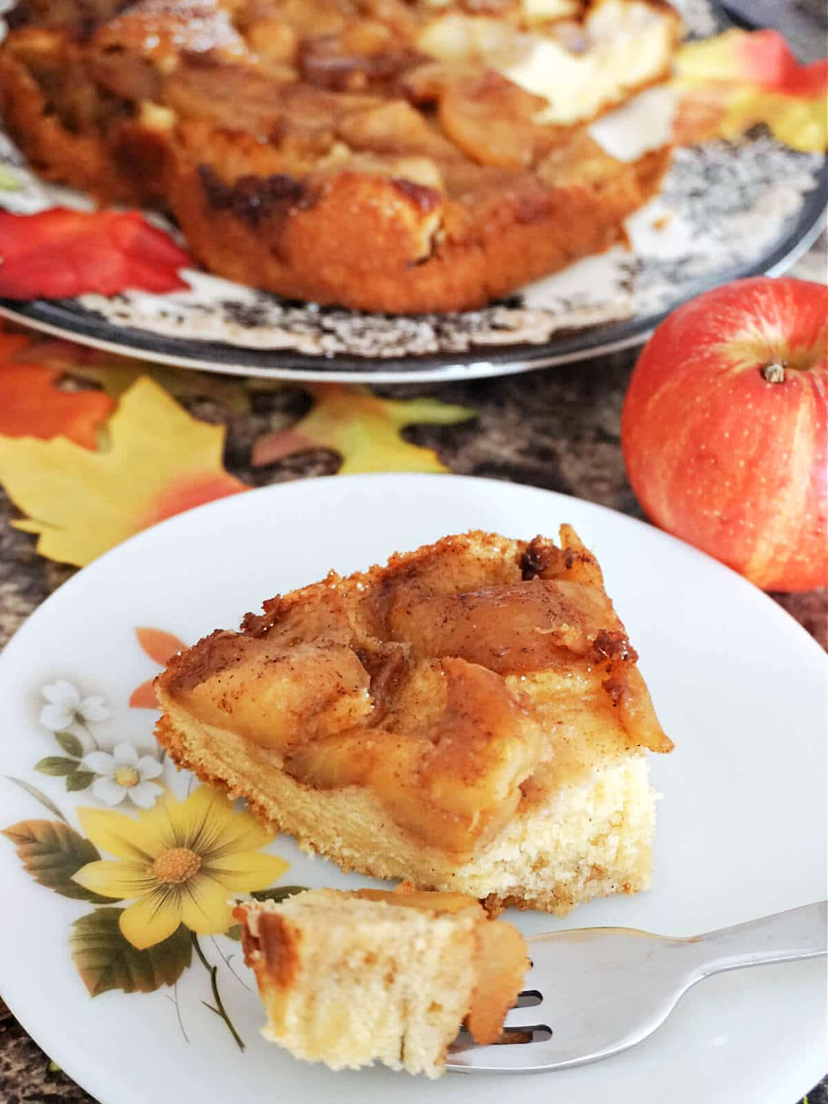 A slice of apple cake on a white plate with more cake in the background