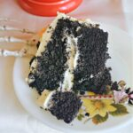 A slice of black velvet cake with frosting on a white plate