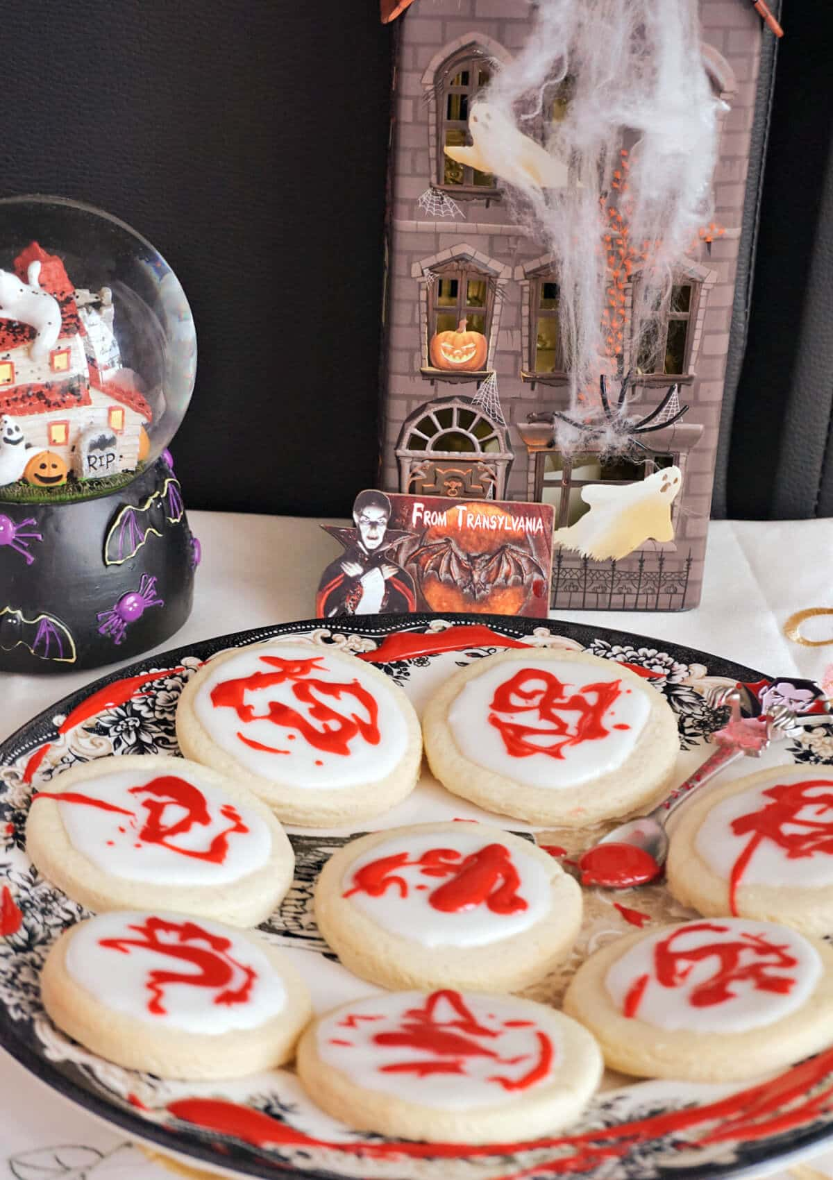 A plate with 8 halloween cookies and decorations around