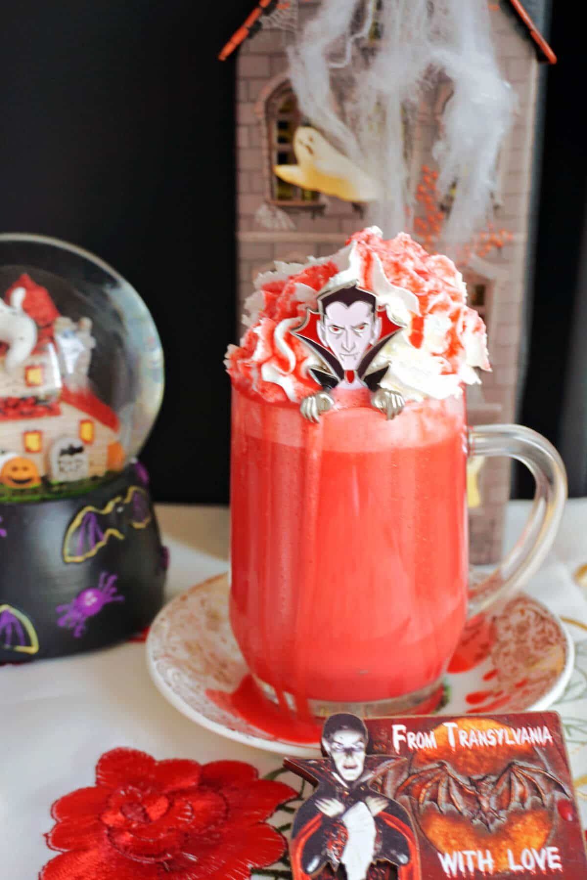 A glass of red hot chocolate with Halloween decorations around