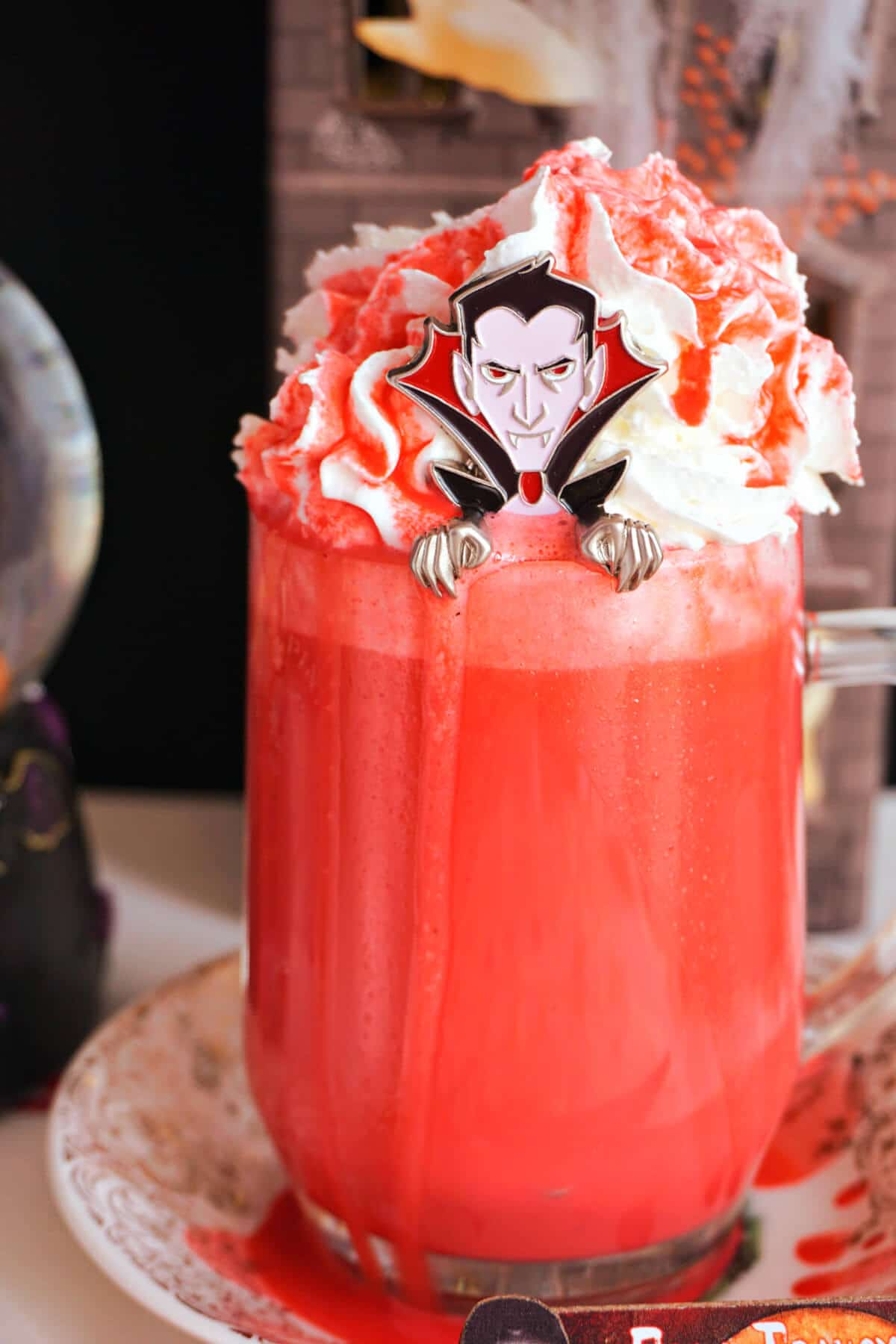 A glass of red hot chocolate with a dracula spoon in it