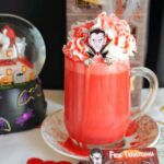 A glass of red hot chocolate topped with cream and halloween decorations around