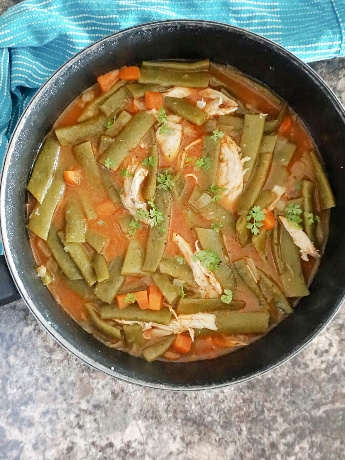 Overhead shoot of a pan with green bean stew with shredded chicken pieces