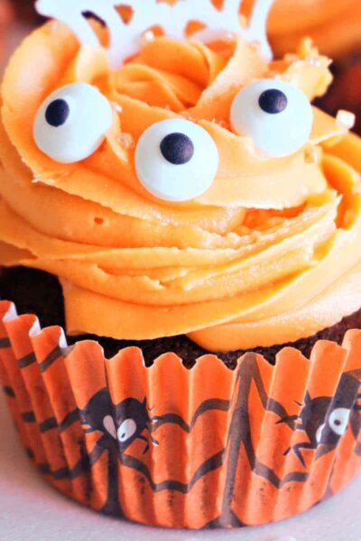 A Halloween cupcake with orange frosting and 3 edible eyes