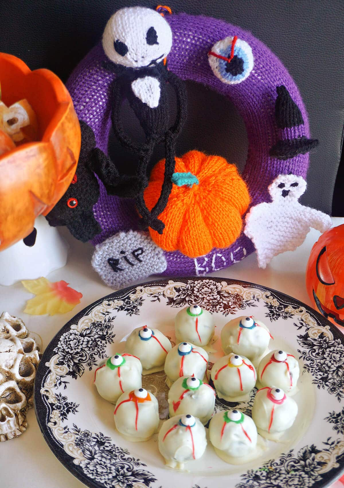 A plate with eyeball truffles surrounded by Halloween decorations