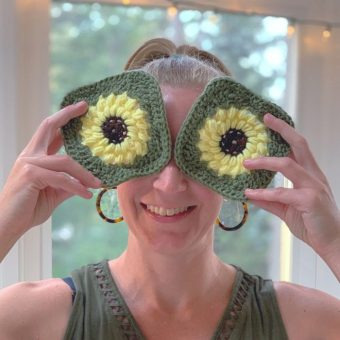A woman holds up two crocheted granny squared in front of her fact to look like eyes. The squares are designed to look like sunflowers. They have brown centers, yellow petals and green edging.