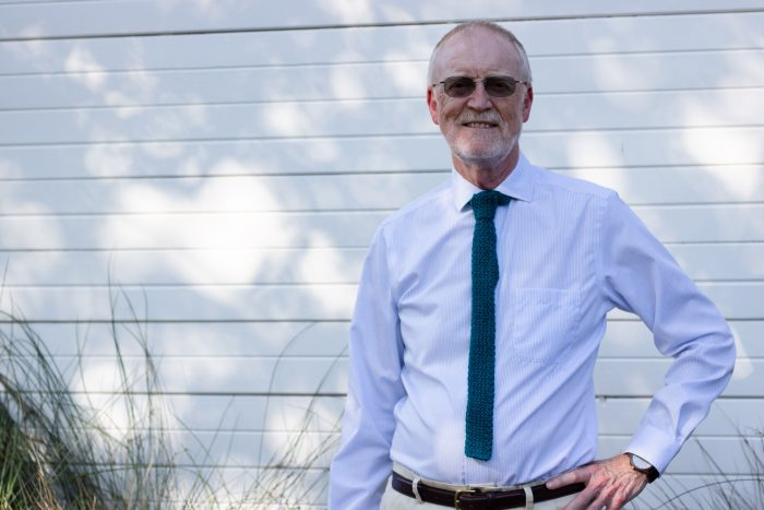 An older man stands in front of a white wall outdoors with his hand on his hip. He is wearing a light blue shirt and a dark teal knitted necktie.