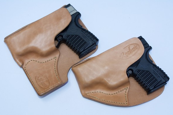 A pair or Springfield Armory XD-S pistols with Recluse holsters. The one on the left is designed for larger cargo style pockets.