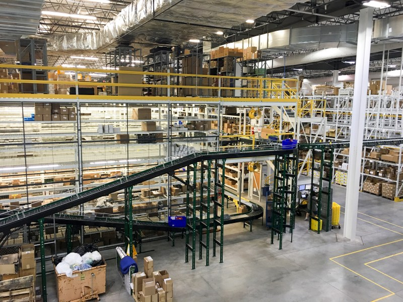 The part of the warehouse that stocks smaller items is three stories tall. Automated conveyors weave through that, allowing pickers to drop items into bins. The system moves bins to the next relevant area based on what items are on the orders.