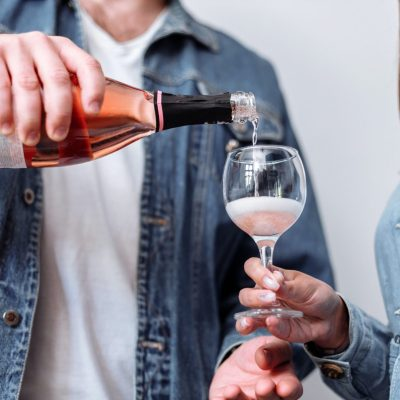 a guy pouring rose wine alcohol for a woman