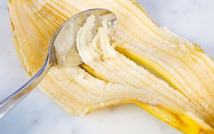A spoon scraping the inside of a banana shell
