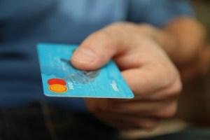 クレジットカードを差出す手とカードのアップ