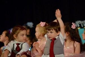 幼児の集まりの中一人だけ手を挙げる男の子