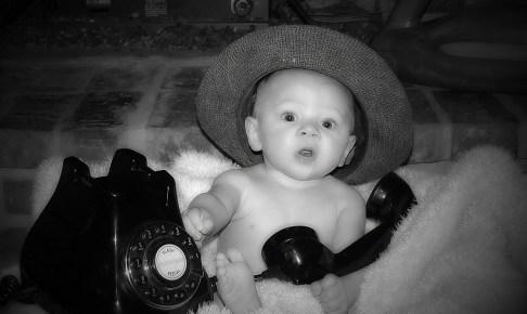 黒い固定電話で遊んでびっくりする赤ちゃん