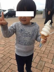 ソフトクリームを持つ男児がピースしてます