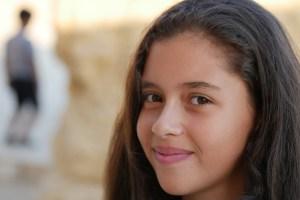 右前に微笑む女の子の顔がアップで映る画像