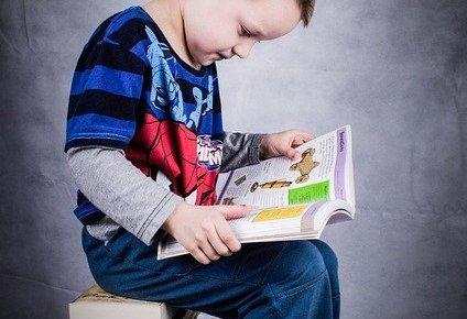 少年が沢山の本の上に座って、本を開いて読んでいます