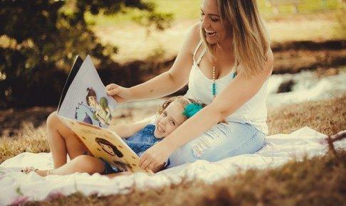 屋外で母と娘が本を観てます