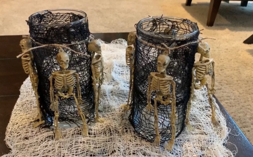 Halloween Decorations DIY: Dollar Tree Skeletons tied onto black mesh covered vase with candle