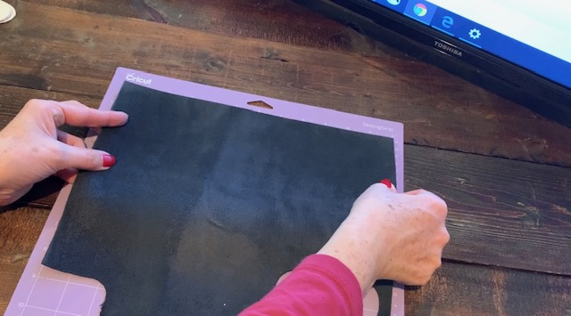 placing genuine leather on a Cricut mat to cut leather earrings on a Cricut