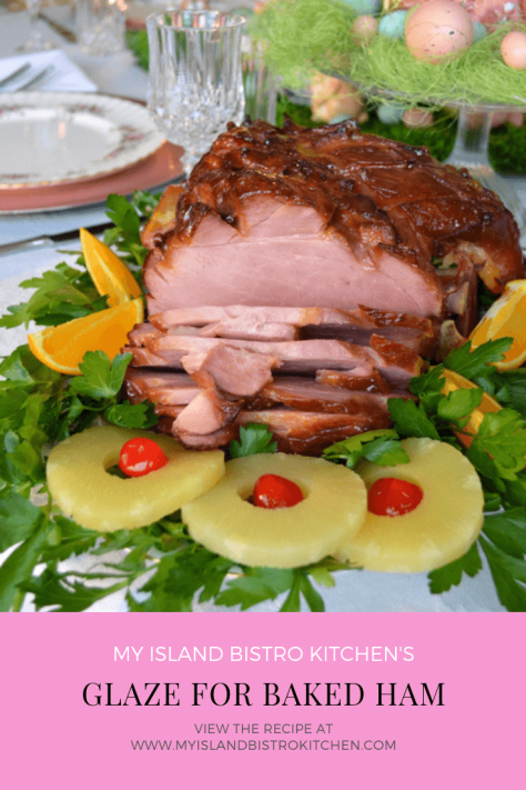 Glazed Baked Ham on a bed of greens surrounded by orange wedges and pineapple slices