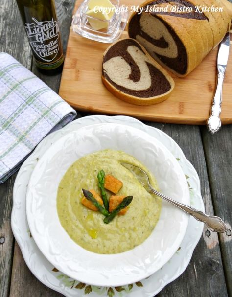 White bowl filled with Cream of Roasted Asparagus Soup with marble rye bread on breadboard in background