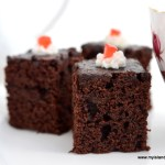 Three chocolate brownies with a dob of icing and red cherries set against a white background