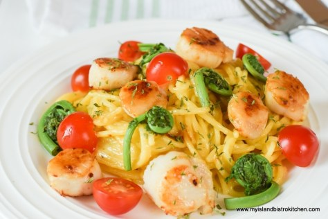 Close up of plate of carbonara with seared scallops, red cherry tomatoes, and green fiddleheads