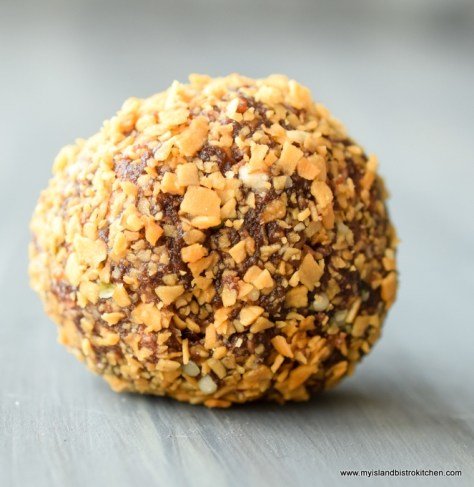 Single Chocolate Almond Bliss Ball covered in toasted coconut and sitting on gray table