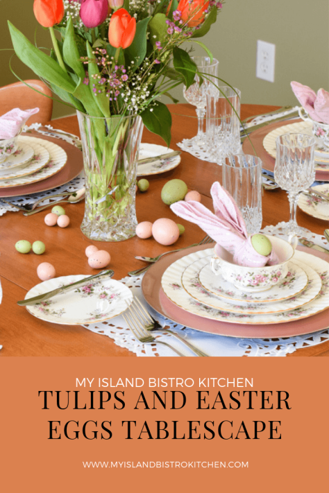 "Easter-themed tablesetting with Royal Albert ""Lavender Rose"" dinnerware on pink charger plates. Napkin fold is the bunny ear fold with pink napkins. A large crystal vase of pink and orange tulips is in center of table."
