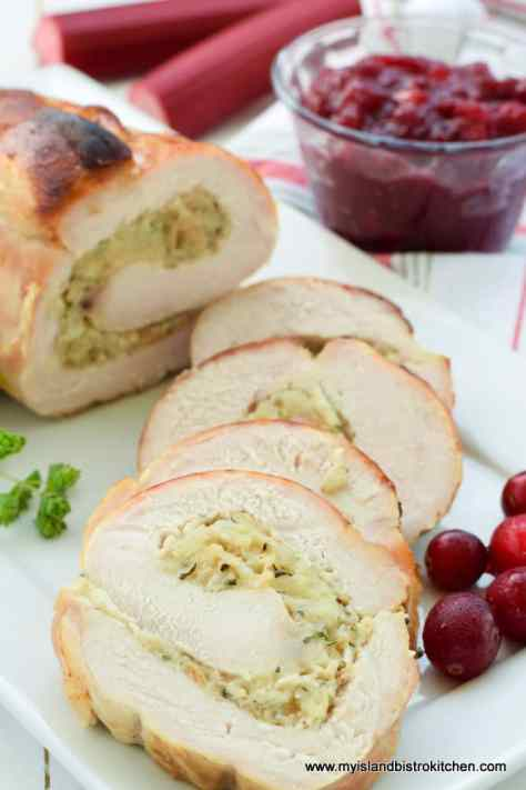 Slices of rolled stuffed turkey breast with small glass bowl of Cranberry Rhubarb Sauce