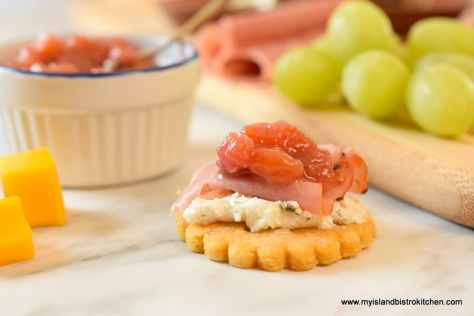 Cracker topped with goat cheese, deli meat, and rhubarb and mango chutney