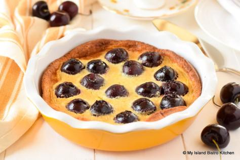 Yellow ceramic pie plate filled with Cherry Clafoutis