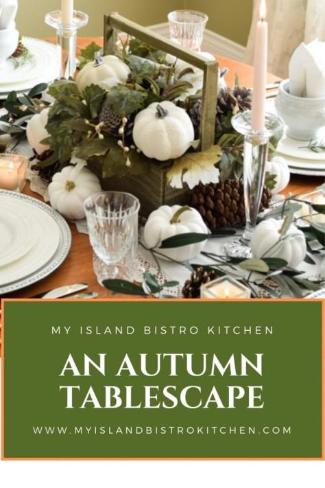 Miniature white pumpkins, muted shades of greenery, and pinecones are the focus of this stylish autumn tablesetting